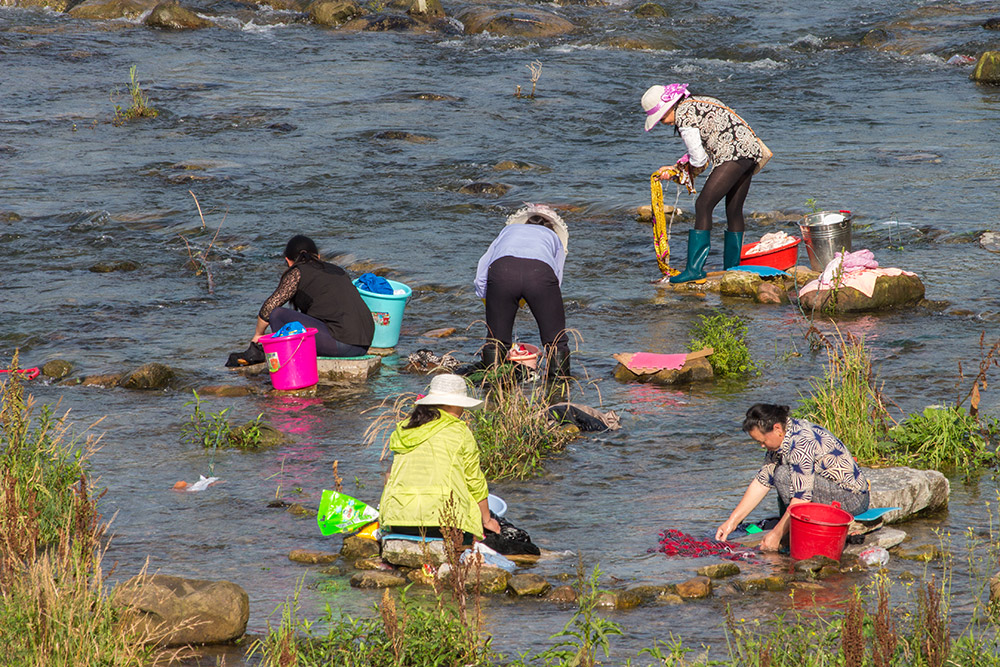 Women washing their clothes in the river in Wulingyuan