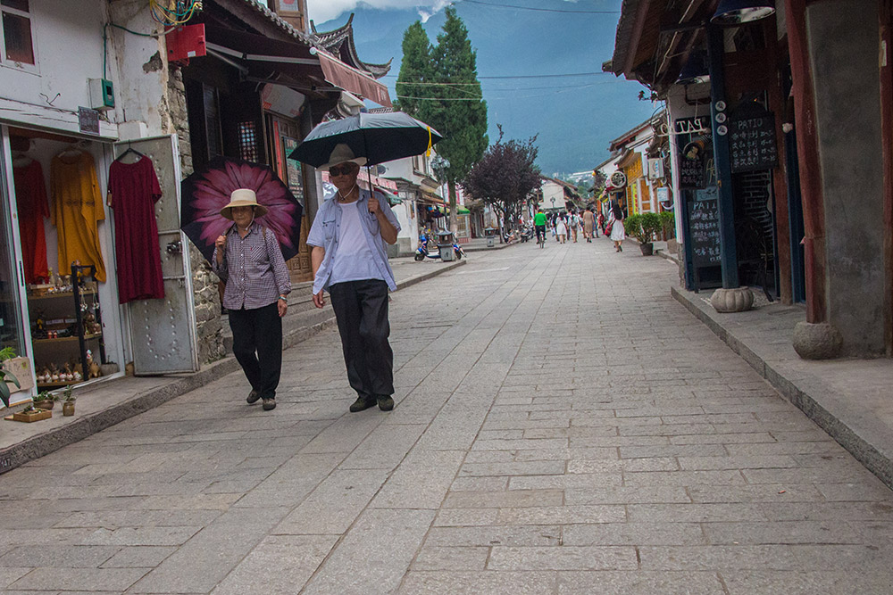 Two older Chinese people walking in the streets of Dali